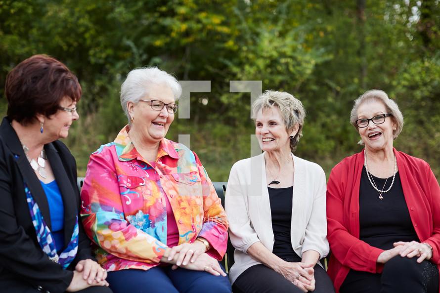 elderly women talking sitting on a bench outdoors