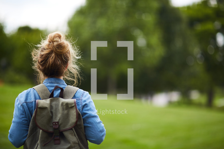 a woman with a backpack standing with her back to the camera
