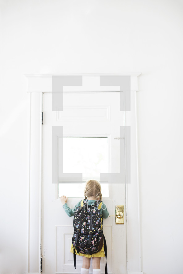 girl child with a book bag looking in a door