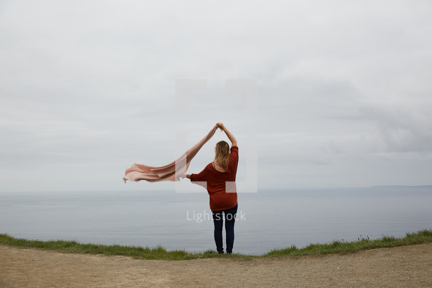 a woman standing at the edge of a cliff taking in the view of the ocean below