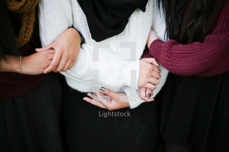 Three friends holding hands