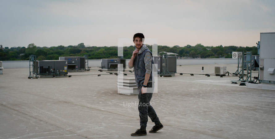 a man standing on a roof and air condition units