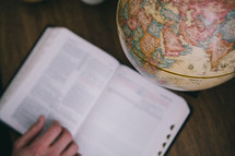 An open Bible next to a globe.