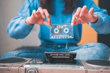 woman holding a broken cassette tape