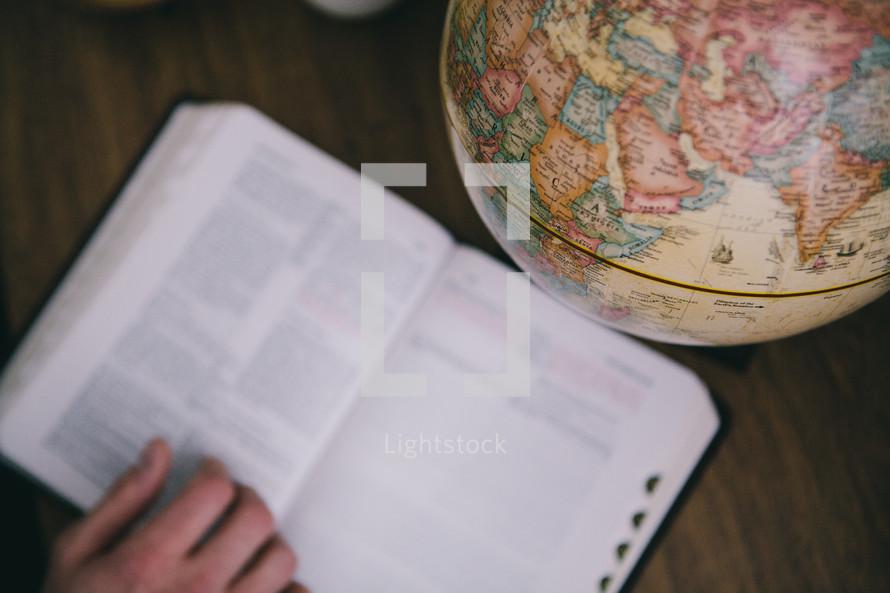 An open Bible next to a globe.
