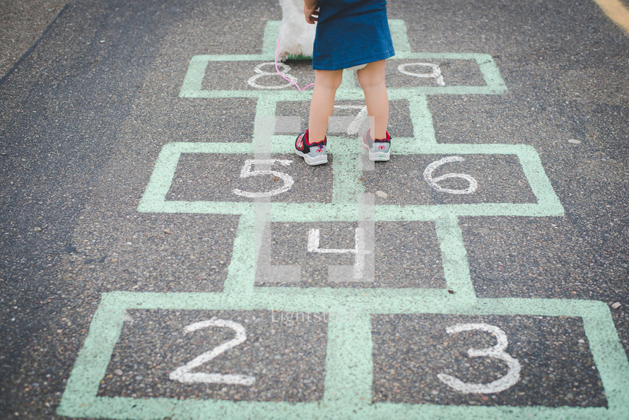 A young girl standing on a hopscotch board with a stuffed animal.