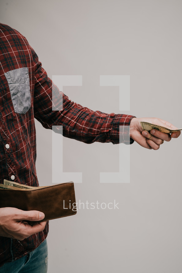 a man pulling money out of his money to pay