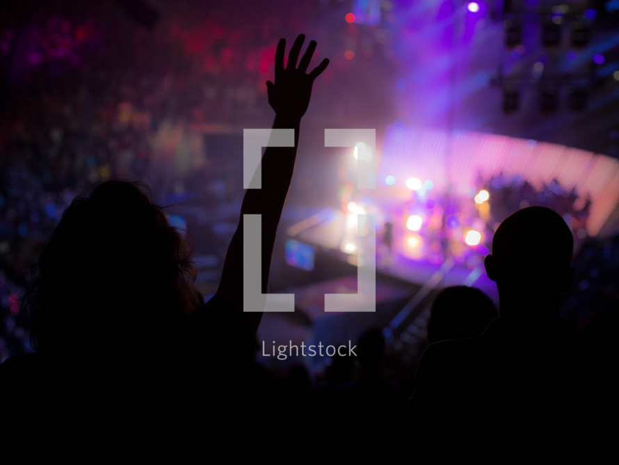 silhouette of a woman with raised arms at a concert