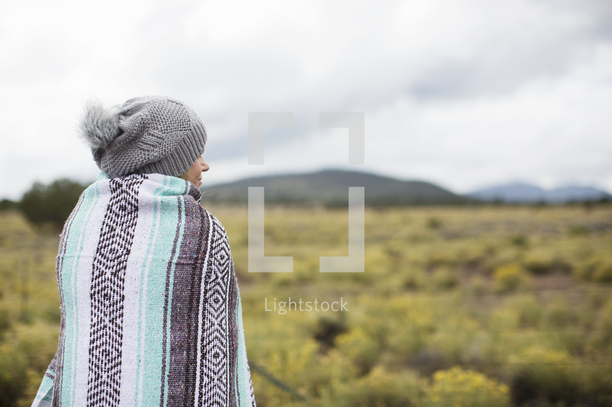 A woman wrapped in a blanket looks out over a field toward mountains.
