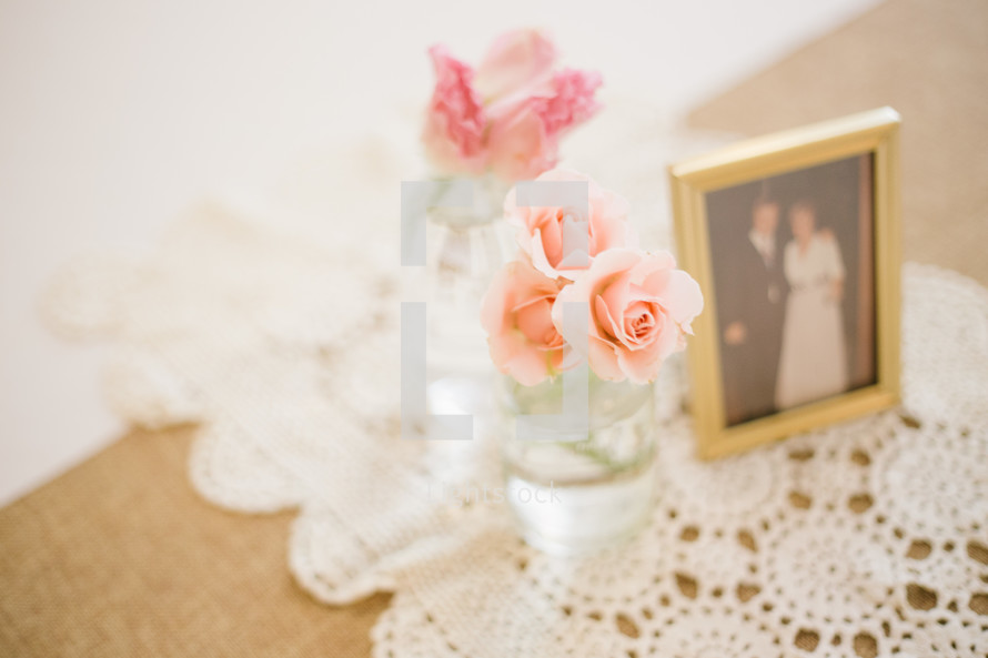 Flowers in vases on a table by a photograph of a couple.
