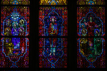 Depictions of Jesus and Mary on three stained glass windows.