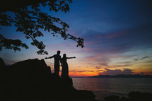 silhouettes of a couple with outstretched hands