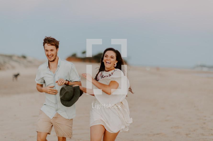 a playful couple running on a beach