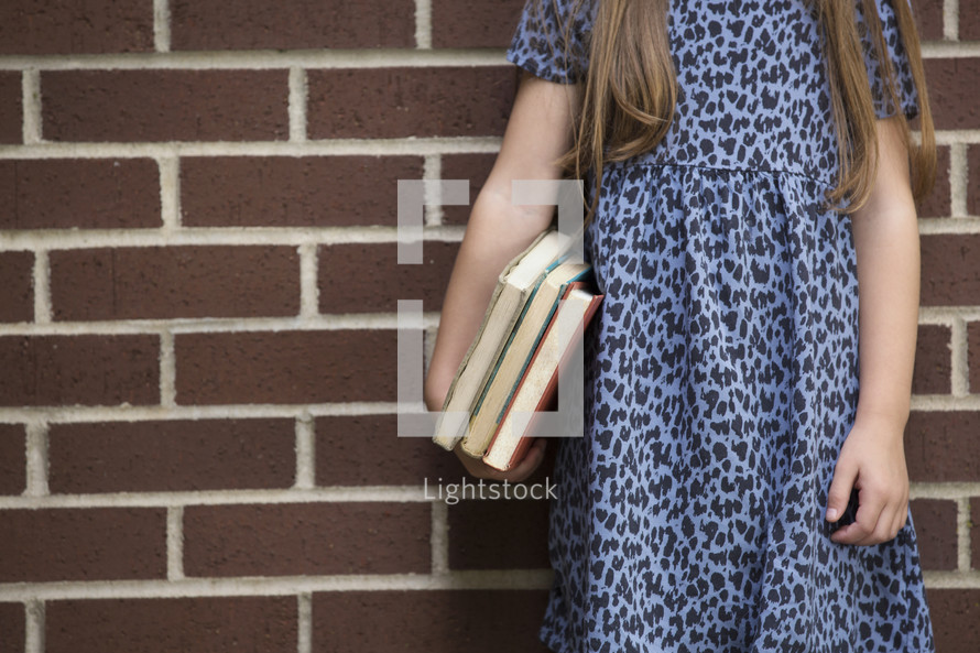 a little girl holding a stack of books