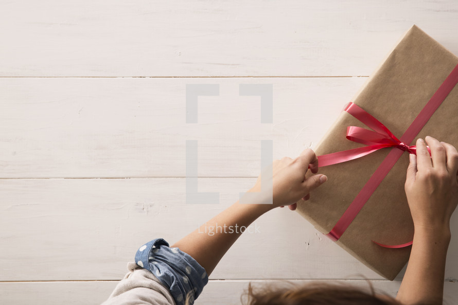 a woman wrapping a Christmas present