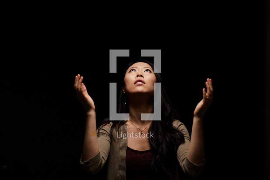 a woman with arms raised praising God