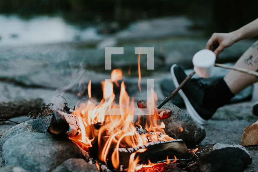 cooking hotdogs over a campfire