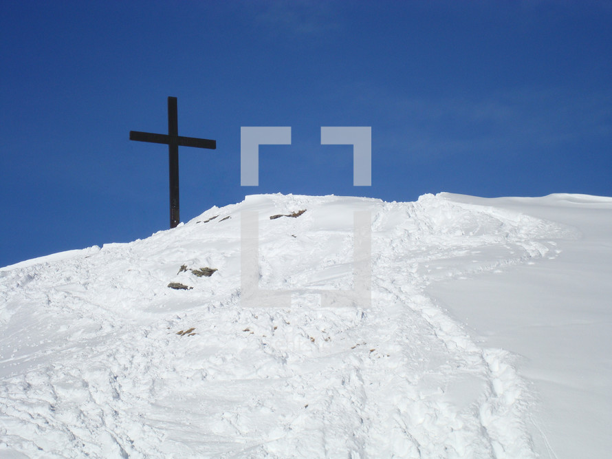 Cross on a snow-covered mountain top,