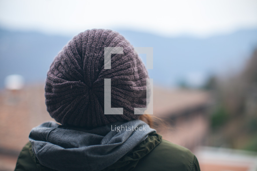 back of a woman's head as she looks out at a European town