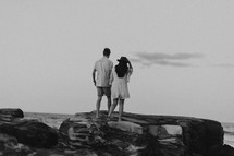 a couple walking on a rocky beach