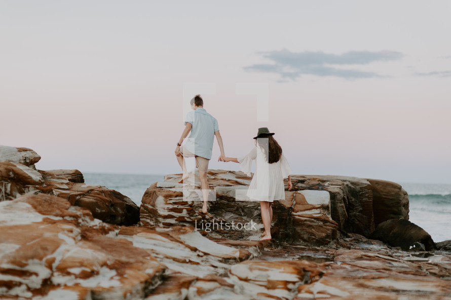 a couple walking holding hands on a beach