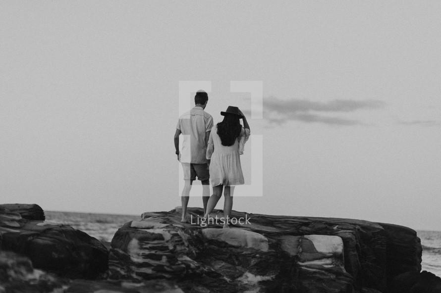 a couple walking on a rocky beach