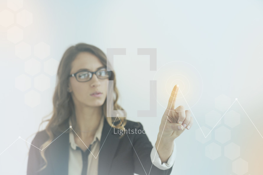 A businesswoman pointing at a graph with her finger.