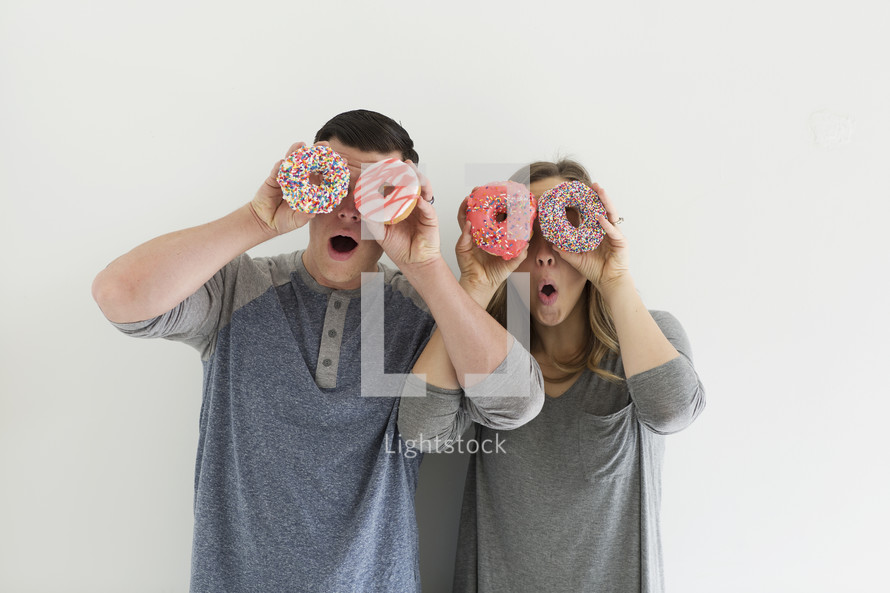 a couple holding sprinkled donuts acting silly
