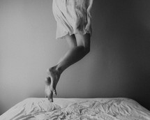 a woman jumping on a bed