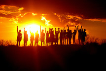 Young people silhouetted holding up their arms