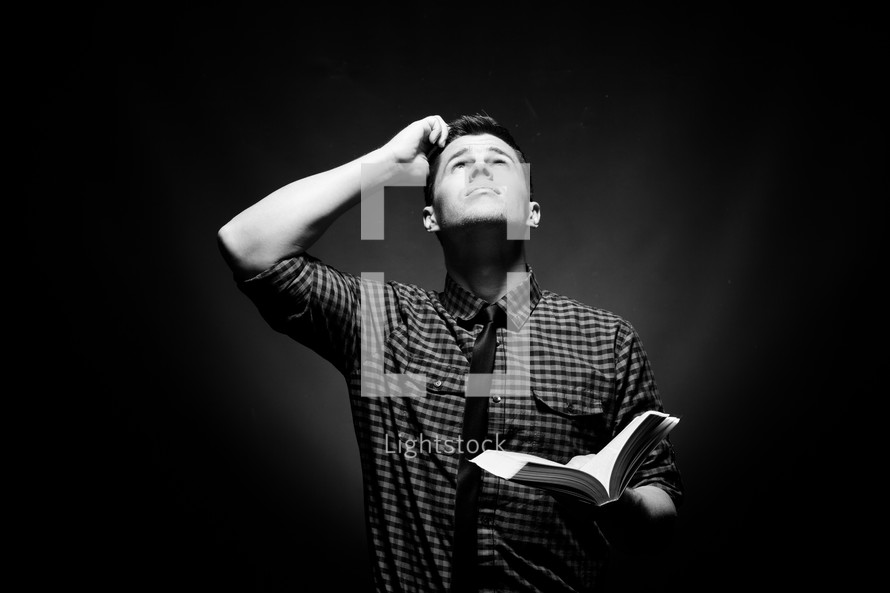 a man holding a Bible and scratching his head looking up to God
