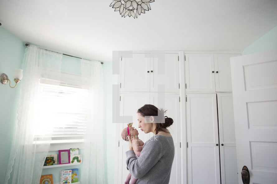 Mother holds infant daughter in white nursery room.