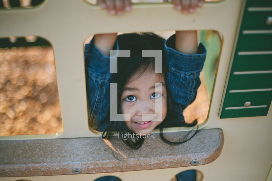 A little girl climbing on playground equipment.