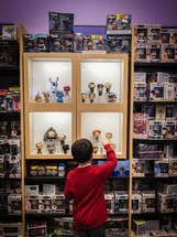 a child in a toy store shopping for collectibles