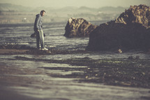 A man standing on a rocky shore.