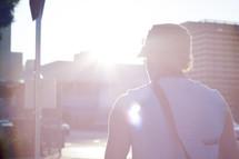 man walking on a street under the glow of sunlight