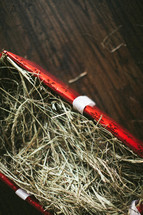 box of straw wrapped in Christmas paper - manger