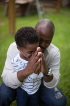 father and son praying together
