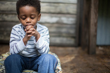 toddler boy sitting with praying hands