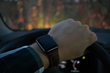 smartwatch on the wrist of an man behind a steering wheel driving