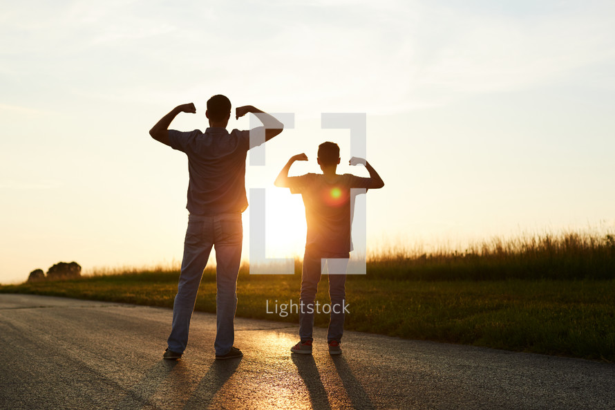 a father and son showing their muscles