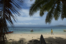 Boy walking on beach with boats and palm trees.