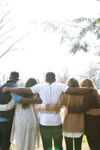 group of friends embracing with their backs to the camera