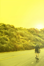 man riding a bicycle on the street at sunrise