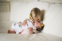 big sister kissing her baby sister