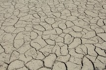 Parched clay soil in a dry lake bed during a drought