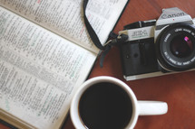 coffee mug, camera, and open Bible