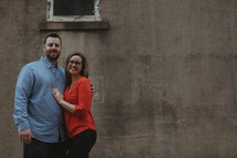 a couple standing together in front of a concrete wall