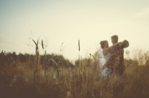 a bride and groom hugging in a field