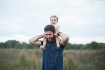 toddler girl on father's shoulders